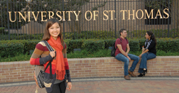 University of St. Thomas Asian undergraduate student standing in front of an entrance to the University with the University name on the black gate in the background