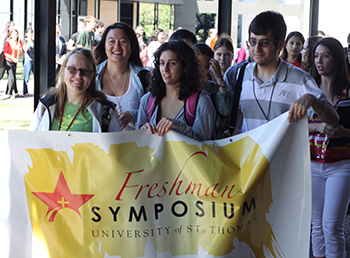 Students with Freshman Symposium banner