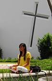 University of St. Thomas Houston student sitting in front of Catholic Chapel of St. Basil