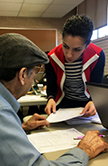 VITA volunteer Anush Hayrapetyan helps a client with his taxes