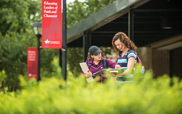 Two female students looking at a book as they walk on campus at the University of St. Thomas in Houston, Texas