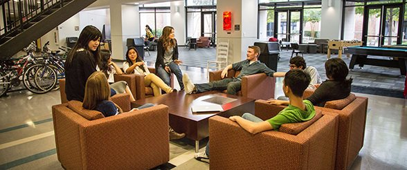 Students sitting on comfortable furniture in lobby of Guinan residence hall dorm at University of St. Thomas in Houston, Texas