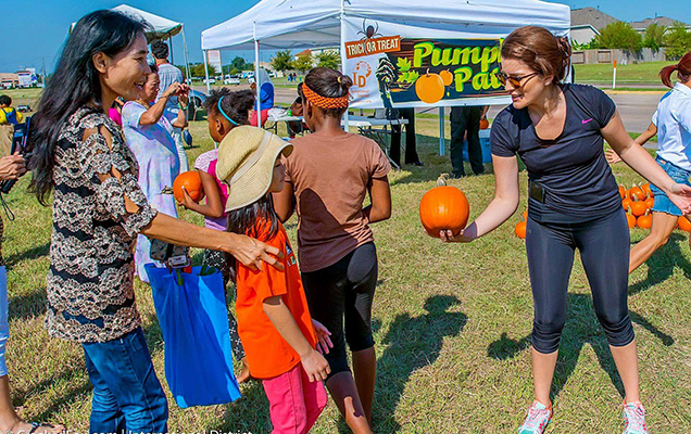 Master of Public Policy and Administration grad Natali Hurtado from UST Houston passes out pumpkins at the Hawes Hill & Associates Fall Festival
