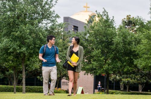 Two undergraduate students walking on campus at the University of St. Thomas in Houston, Texas with the Catholic Chapel of St. Basil visible in the background