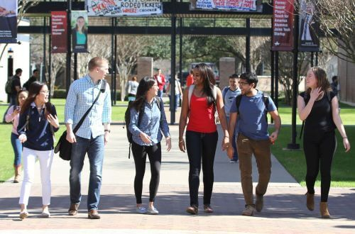 Diverse group of undergraduate students walking on campus at University of St. Thomas in Houston, Texas