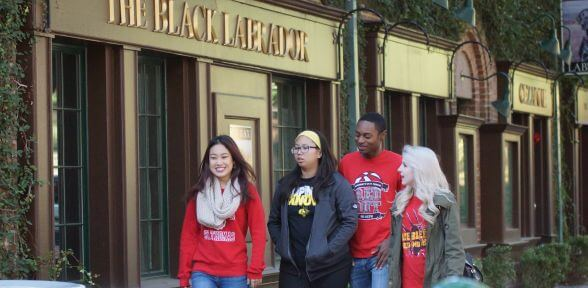 University of St. Thomas students walking past the Black Labrador restaurant and British pub in the Montrose neighborhood of Houston, Texas
