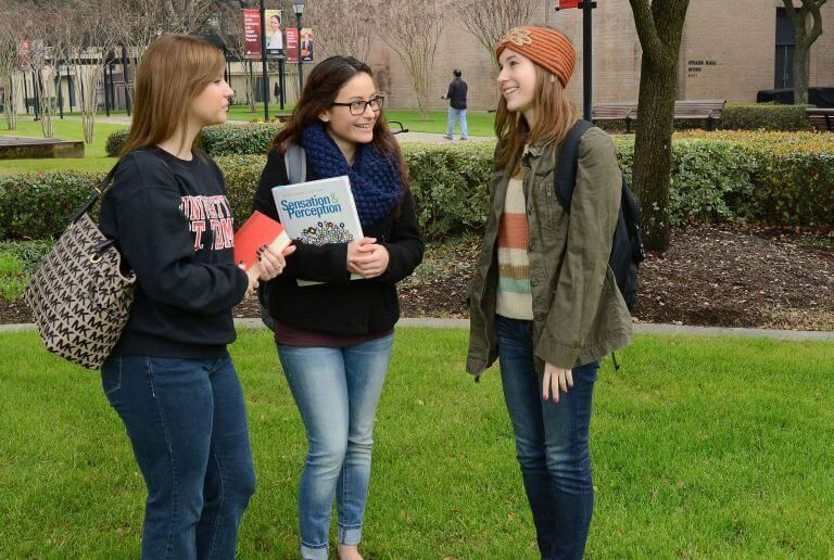 Three female undergraduate students outside on campus during the fall semester at the University of St. Thomas in Houston, Texas