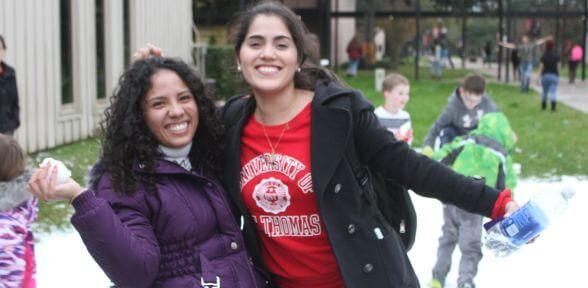 Two undergraduate students, with one holding a snowball during the Deck the Mall holiday celebration at the University of St. Thomas in Houston, Texas