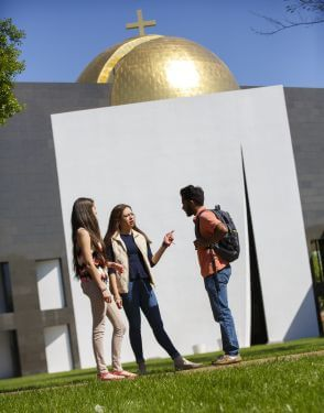 Undergraduate students talking in front of Chapel of St. Basil at the University of St. Thomas in Houston, Texas