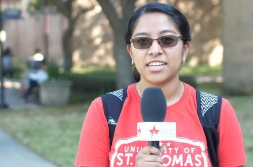 Undergraduate student speaking into microphone on the campus of the University of St. Thomas in Houston, Texas