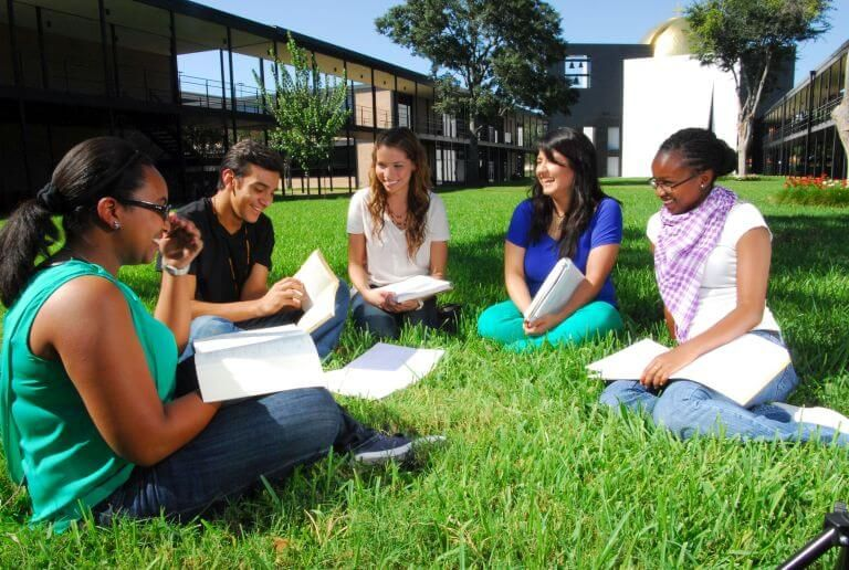 Undergraduate students sitting with books on academic mall during summer classes at the University of St. Thomas in Houston, Texas