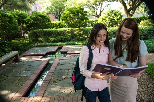 Two female students review notes on the University of St. Thomas - Houston campus