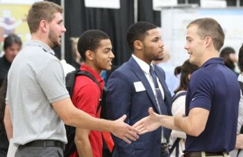 Students shake hands at a job fair at University of St. Thomas - Houston