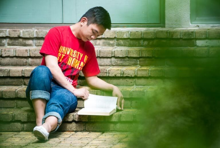 University of St. Thomas Houston student reading a book