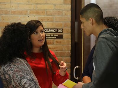 Hispanic student talking with adviser during Camino a UST event at University of St. Thomas in Houston, Texas
