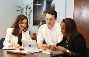 Three University of St. Thomas - Houston business major students work at laptop