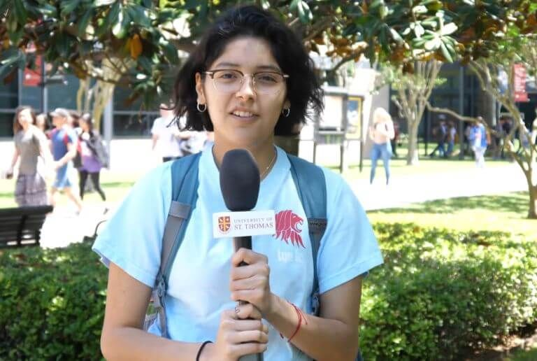 Student holding microphone on campus of University of St. Thomas in Houston, Texas