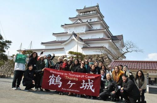 University of St. Thomas students standing in front of Aizuwakamatsu Castle during study abroad trip to Japan