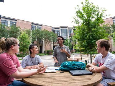 Group of University of St. Thomas - Houston History majors sit at table on campus