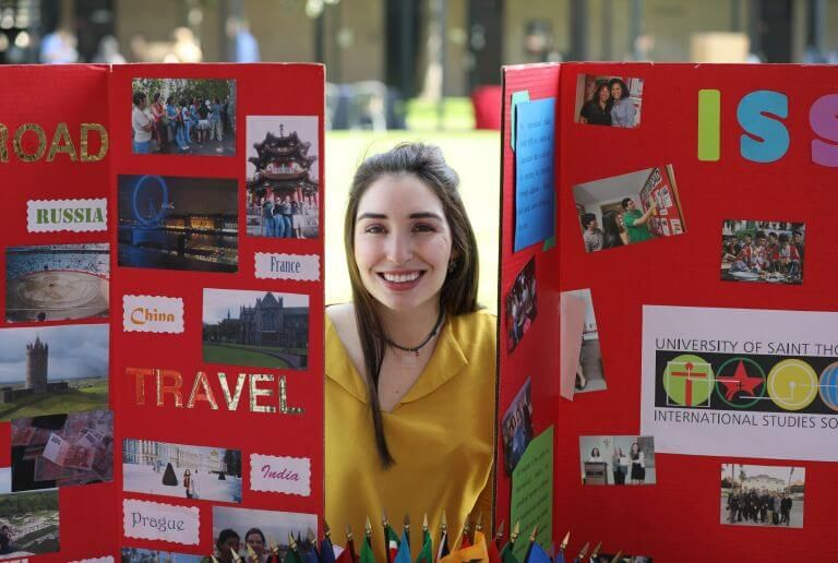 Undergraduate student poses during club fair at University of St. Thomas in Houston, Texas