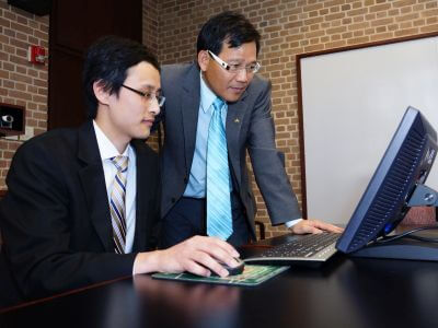 University of St. Thomas - Houston MBA in Management Information Systems student works at computer with professor