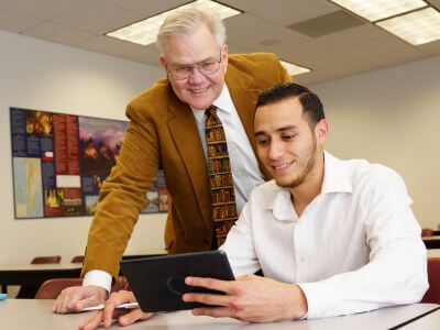 University of St. Thomas - Houston MBA in Health Care Administration student works on tablet with professor