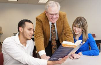 Two University of St. Thomas - Houston MSA Master of Science in Accounting students look at book with professor