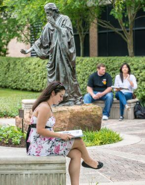 Psychology major studies in front of Jesus sculpture on University of St. Thomas - Houston campus