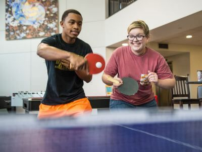 Students playing ping pong inside Guinan Hall dorm at University of St. Thomas in Houston, Texas