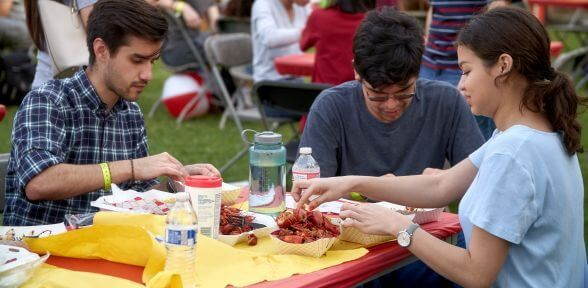 Three students during annual Crawfish Boil at University of St. Thomas in Houston, Texas