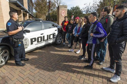 UST police officer speaks to University of St. Thomas - Houston Criminology majors in front of police car