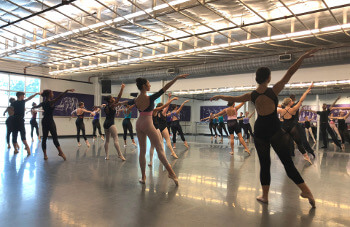 Large group of University of St. Thomas - Houston dance majors practice in the studio