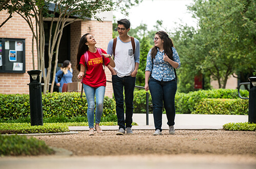 Three students walk on campus at University of St. Thomas in Houston, Texas