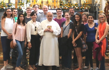 University of St. Thomas - Houston MA in John Paul II Studies students with priest in church in Poland