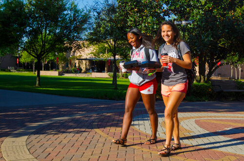 University of St. Thomas - Houston two female undergraduate students walk on campus