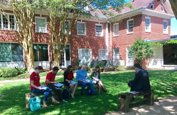 Students sit with professor outside University of St. Thomas - Houston Honors Program House