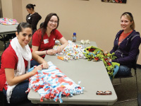 Volunteers making fleece blankets for children for Project Linus.